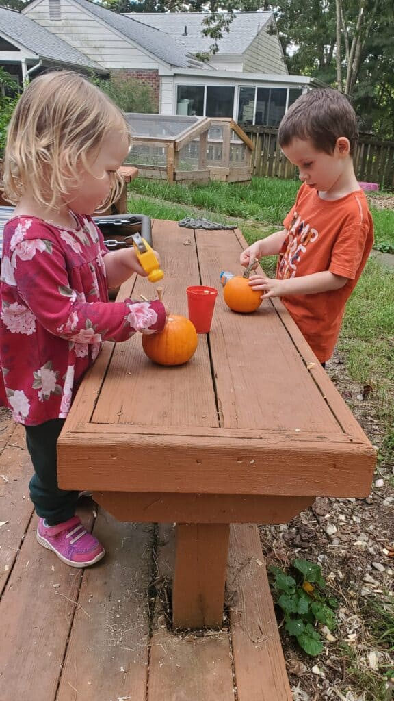 Hammering Pegs into Pumpkins in our Nature-Based Homeschool Preschool